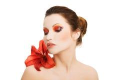 Πορτρέτο της νέας γυναίκας με το κόκκινο λουλούδι κρίνων Στοκ φωτογραφία με δικαίωμα ελεύθερης χρήσης