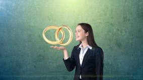 Πορτρέτο της νέας γυναίκας που κρατά τα χρυσά γαμήλια δαχτυλίδια στην ανοικτή παλάμη χεριών, απομονωμένο υπόβαθρο στούντιο χρυσή  Στοκ εικόνα με δικαίωμα ελεύθερης χρήσης