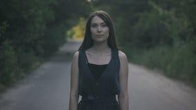Πορτρέτο της νέας γυναίκας που στέκεται στο δρόμο σε ένα δασικό κλίμα απόθεμα βίντεο