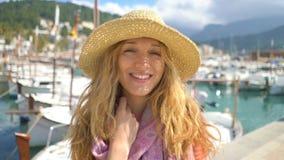 Πορτρέτο της νέας γυναίκας που φορά το καπέλο αχύρου που χαμογελά στη κάμερα με seacoast το υπόβαθρο απόθεμα βίντεο