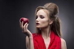 Πορτρέτο της νέας γυναίκας σε ένα κόκκινο μαντίλι με μια εμπροσθοφυλακή hairstyle που κρατά το διαθέσιμο κόκκινο μήλο σε ένα γκρί Στοκ Εικόνες