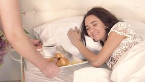 Πορτρέτο της νέας γυναίκας ύπνου που παίρνει τον καφέ της στο κρεβάτι από το φροντίζοντας σύζυγό της απόθεμα βίντεο