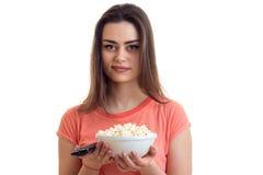 Πορτρέτο της νέας γυναίκας brunette με τη TV μακρινή και pop-corn στα χέρια Στοκ Εικόνες