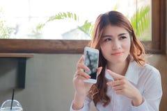Πορτρέτο της νέας ελκυστικής ασιατικής επιχειρησιακής γυναίκας που κρατά το κινητό έξυπνο τηλέφωνο και που εξετάζει τη κάμερα στη στοκ εικόνες