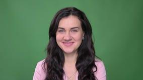 Πορτρέτο της νέας επιχειρηματία brunette στο ρόδινο σακάκι που χαμογελά δειλά στη κάμερα στο πράσινο υπόβαθρο απόθεμα βίντεο