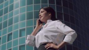 Πορτρέτο της νέας επιχειρησιακής γυναίκας που κάνει ένα τηλεφώνημα και που μιλά smilingly φιλμ μικρού μήκους