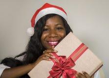 Πορτρέτο της νέας ευτυχούς και όμορφης αμερικανικής γυναίκας μαύρων Αφρικανών στο καπέλο Άγιου Βασίλη που κρατά το παρόν χαμόγελο στοκ εικόνες με δικαίωμα ελεύθερης χρήσης