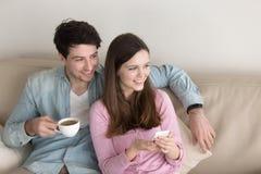 Πορτρέτο της νέας ευτυχούς χαλάρωσης ζευγών στο εσωτερικό, που απολαμβάνει τον καφέ Στοκ Φωτογραφίες