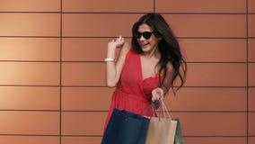 Πορτρέτο της νέας ελκυστικής γυναίκας που εξετάζει τις αγορές της με τον ενθουσιασμό φιλμ μικρού μήκους