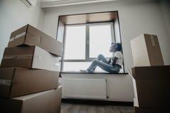 Πορτρέτο της νέας κίνησης γυναικών afro αμερικανικής στη νέα εγχώρια συνεδρίαση στο windowsill sourendet με τα κιβώτια κινούμενων στοκ φωτογραφίες με δικαίωμα ελεύθερης χρήσης