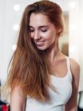 Πορτρέτο της νέας καυκάσιας γυναίκας με τη μακριά δίκαιη τρίχα που κοιτάζει κάτω συνεσταλμένα και που χαμογελά στο κατάστημα ομορ Στοκ φωτογραφία με δικαίωμα ελεύθερης χρήσης