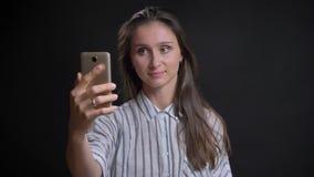 Πορτρέτο της νέας καυκάσιας μακρυμάλλους ομιλίας γυναικών στο videochat που χρησιμοποιεί το smartphone στο μαύρο υπόβαθρο απόθεμα βίντεο