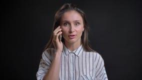 Πορτρέτο της νέας καυκάσιας μακρυμάλλους ομιλίας γυναικών smilingly στο κινητό τηλέφωνο στο μαύρο υπόβαθρο φιλμ μικρού μήκους