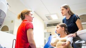 Πορτρέτο της νέας μητέρας που μιλά στον παιδιατρικό οδοντίατρο στην κλινική Στοκ εικόνες με δικαίωμα ελεύθερης χρήσης