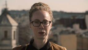 Πορτρέτο της νέας μοντέρνης γυναίκας σχεδιαστών με τα dreadlocks και να διαπερνήσει εξετάζοντας τη κάμερα και χαμογελώντας στην η φιλμ μικρού μήκους