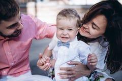 Πορτρέτο της νέας μοντέρνης συνεδρίασης ζευγών στο πεζοδρόμιο σε παλαιό δικοί Όμορφο αγόρι ευχαριστημένο από τους γονείς του στοκ φωτογραφία