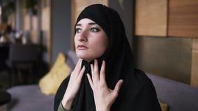 Πορτρέτο της νέας μουσουλμανικής γυναίκας στη συνεδρίαση hijab στον καφέ, που κοιτάζει στην πλευρά και που σκέφτεται, που καθορίζ απόθεμα βίντεο