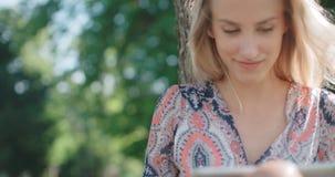 Πορτρέτο της νέας ξανθής γυναίκας που χρησιμοποιεί την ταμπλέτα απόθεμα βίντεο