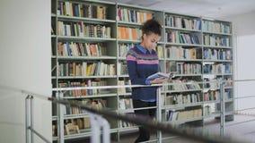 Πορτρέτο της νέας σγουρής γυναίκας αφροαμερικάνων που διαβάζει το παλαιό βιβλίο στεμένος κοντά στα ράφια βιβλίων φιλμ μικρού μήκους