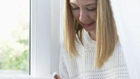 Πορτρέτο της νέας συνεδρίασης γυναικών στη στρωματοειδή φλέβα παραθύρων με το έξυπνο τηλέφωνο και το χαμόγελο απόθεμα βίντεο