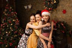 Πορτρέτο της νέας τοποθέτησης γυναικών τρία κοντά στα διακοσμημένα Χριστούγεννα τ στοκ εικόνες