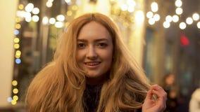 Πορτρέτο της νέας τοποθέτησης γυναικών χαμόγελου που φαίνεται κεκλεισμένων των θυρών υπαίθρια Η κυρία τινάζει την τρίχα της, κλεί απόθεμα βίντεο