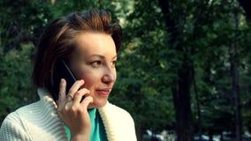 Πορτρέτο της νέας χαριτωμένης ομιλίας κοριτσιών στην κινητή τηλεφωνική συνεδρίαση στο πάρκο το καλοκαίρι απόθεμα βίντεο