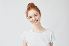 Πορτρέτο της νέας όμορφης γυναίκας πιπεροριζών με τις φακίδες που χαμογελούν cheerfuly την εξέταση τη κάμερα η ανασκόπηση απομόνω Στοκ Φωτογραφία