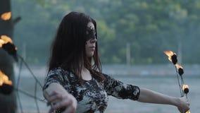 Πορτρέτο της νέας όμορφης γυναίκας στη μάσκα που εκτελεί μια επίδειξη με τη φλόγα που στέκεται στο riverbank μπροστά από τα δέντρ φιλμ μικρού μήκους