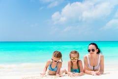 Πορτρέτο της νέας όμορφης μητέρας και των λατρευτών μικρών κορών της στην τροπική παραλία Στοκ Φωτογραφία