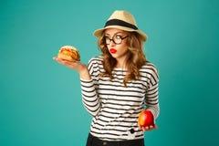 Πορτρέτο της νέας όμορφης ξανθής γυναίκας στο καπέλο που κρατά το κόκκινο μήλο Στοκ εικόνα με δικαίωμα ελεύθερης χρήσης