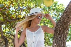 Πορτρέτο της νέας όμορφης προκλητικής γυναίκας με την άσπρη τοποθέτηση καπέλων στο τροπικό δέντρο παραλιών, νησί του Μπαλί Στοκ Φωτογραφίες
