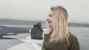 Πορτρέτο της νέας όμορφης στάσης γυναικών στη μαύρη παραλία, κοντά Troll στους βράχους toe στην Ισλανδία και το χαμόγελο, κύμα τρ απόθεμα βίντεο