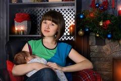 Πορτρέτο της νέας beatuful μητέρας που θηλάζει το μωρό της κοντά στην εστία στη Παραμονή Χριστουγέννων στοκ φωτογραφία με δικαίωμα ελεύθερης χρήσης