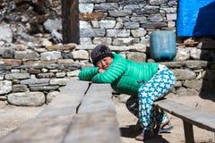 Πορτρέτο της νεπαλικής χαλάρωσης κοριτσιών στον ξύλινο πάγκο Στοκ Εικόνα