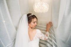 Πορτρέτο της νύφης σε μια ρόμπα κάτω από την άσπρη κουρτίνα στοκ εικόνα
