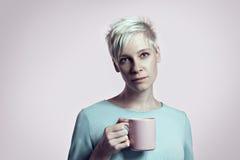 Πορτρέτο της ξανθής γυναίκας με το φλυτζάνι του νερού, σύντομο φωτεινό υπόβαθρο υποβάθρου τρίχας Στοκ φωτογραφίες με δικαίωμα ελεύθερης χρήσης