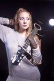 Πορτρέτο της ξανθής καυκάσιας τοποθέτησης γυναικών με την ακουστική κιθάρα Στοκ Φωτογραφίες