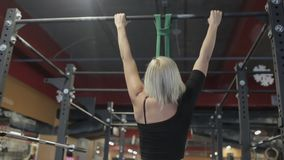 Πορτρέτο της ξανθής φιλάθλου, η οποία κάνει το πηγούνι-UPS στο φραγμό στη σύγχρονη γυμναστική φιλμ μικρού μήκους