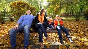 Πορτρέτο της οικογένειας με δύο παιδιά που κάθονται σε έναν πάγκο στο όμορφο πάρκο φθινοπώρου φιλμ μικρού μήκους