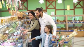 Πορτρέτο της οικογένειας που επιλέγει το ψωμί και τα γλυκά στο τμήμα αρτοποιείων στην υπεραγορά απόθεμα βίντεο
