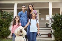 Πορτρέτο της οικογένειας που στέκεται μπροστά από το σπίτι με το σκυλί της Pet στοκ εικόνα με δικαίωμα ελεύθερης χρήσης