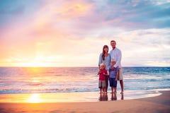 Πορτρέτο της οικογένειας στην παραλία στο ηλιοβασίλεμα Στοκ Εικόνες