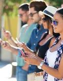Πορτρέτο της ομάδας φίλων που έχουν τη διασκέδαση με τα smartphones Στοκ Εικόνες
