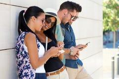 Πορτρέτο της ομάδας φίλων που έχουν τη διασκέδαση με τα smartphones Στοκ Φωτογραφία