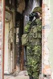 Πορτρέτο της οπλισμένης γυναίκας με την κάλυψη Ο νέος θηλυκός στρατιώτης παρατηρεί με το πυροβόλο Στοκ Φωτογραφία