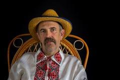 Πορτρέτο της ουκρανικής συνεδρίασης χωρικών σε μια ψάθινη καρέκλα Στοκ Εικόνες