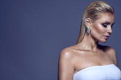 Πορτρέτο της πανέμορφης κομψής ξανθής γυναίκας με την υγρή καλλιτεχνική σύνθεση τρίχας και να λάμψει που φορά την άσπρη τοπ και π στοκ φωτογραφία