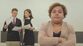 Πορτρέτο της παχουλής γυναίκας στην επίσημη ένδυση που κοιτάζει στη κάμερα στο πρώτο πλάνο στο γραφείο ενώ το αρσενικό και το θηλ απόθεμα βίντεο