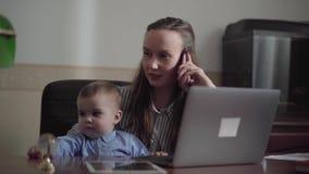 Πορτρέτο της πολυάσχολης αρκετά νέας μητέρας που συνεργάζεται στο σπίτι με το μωρό στις περιτυλίξεις της Η γυναίκα που μιλά από τ απόθεμα βίντεο